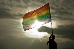 A person holds a rainbow flag during the Gay Pride Parade in San Salvador, El Salvador, on June 28, 2014. AFP PHOTO/ Jose CABEZAS